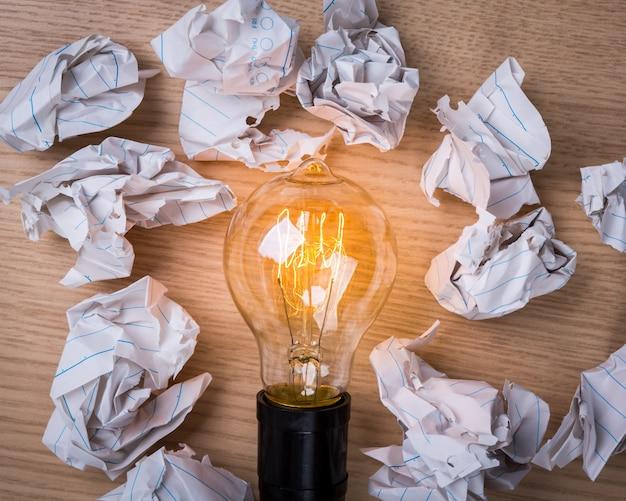 Boules de papier avec une ampoule allumée