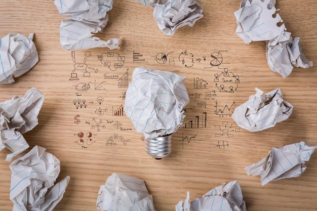 Boules de papier avec une ampoule et des formules ci-dessous le papier