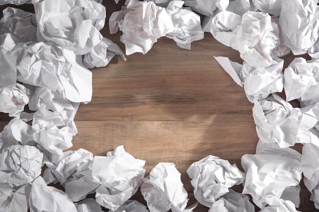 Boules de papier froissé sur fond en bois.