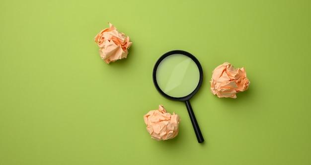 Boules de papier froissé et loupe en plastique noir sur une surface verte. concept de recherche d'idées et de solutions, diverses options, pose à plat