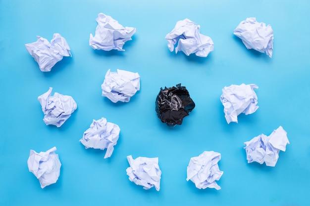 Boules de papier froissées blanches et noires sur fond bleu.