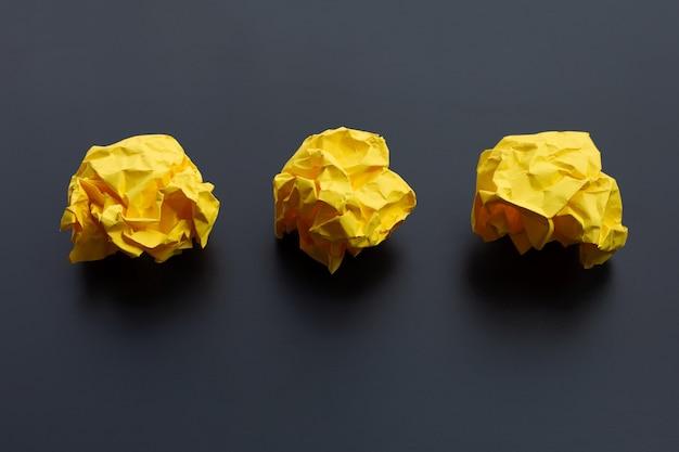 Boules de papier jaune froissé sur une surface sombre. copier l'espace