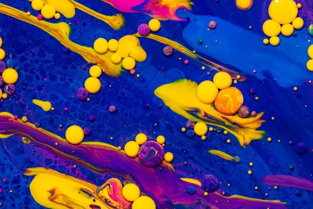 Boules de peinture acrylique texture abstraite mélange de liquides bleus et jaunes violets