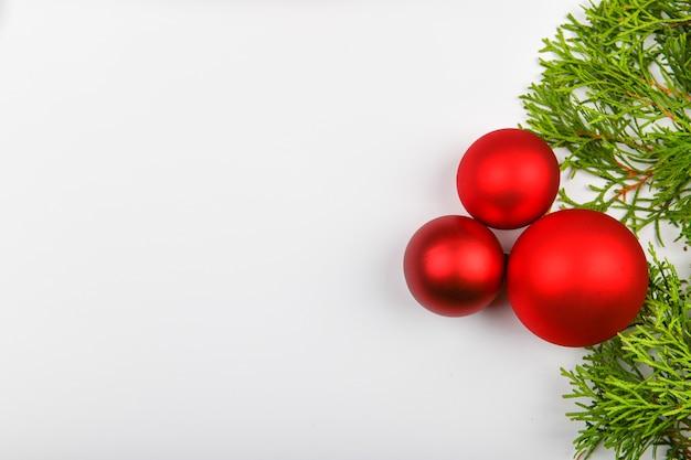 Boules rouges sur les branches vertes, espace blanc. emballage cadeau avec un arc rouge sur un espace blanc. vue d'en-haut. place pour l'écriture. espace de noël.