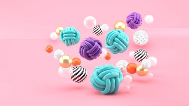 Boules de tissu parmi les boules colorées sur l'espace rose