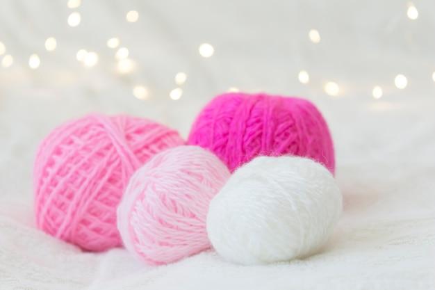 Boules de tricot rose se trouvent sur un fond jaune bokeh