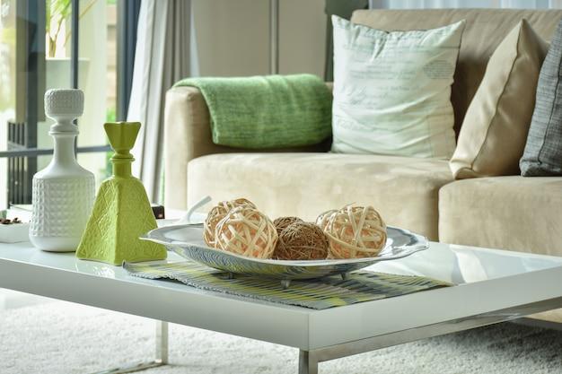 Boules et vases ratten sur table supérieure blanche avec canapé marron clair