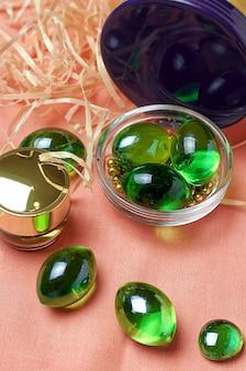 Boules de verre vertes sur tissu rose avec des pots dorés