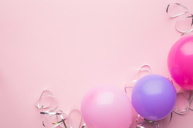 Boules violettes, roses et serpentine argentée sur fond de papier rose. fond de vacances. espace copie