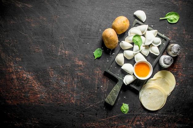 Boulette crue. préparation des boulettes avec pommes de terre et épices sur table rustique sombre