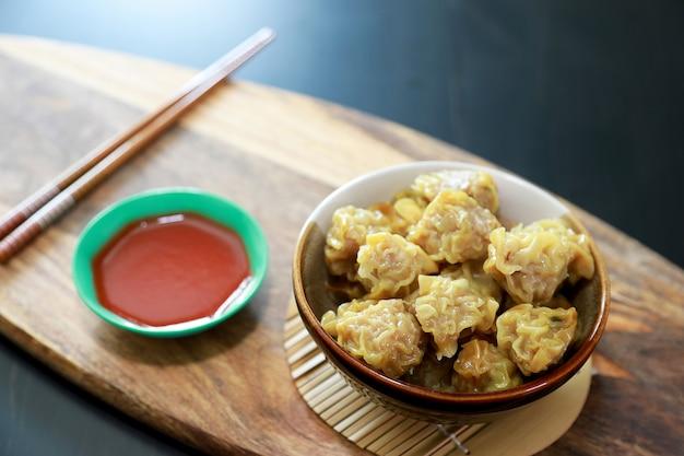 Boulette à la vapeur côtelette de porc dim sum dans le bol avec la sauce dans les tasses.
