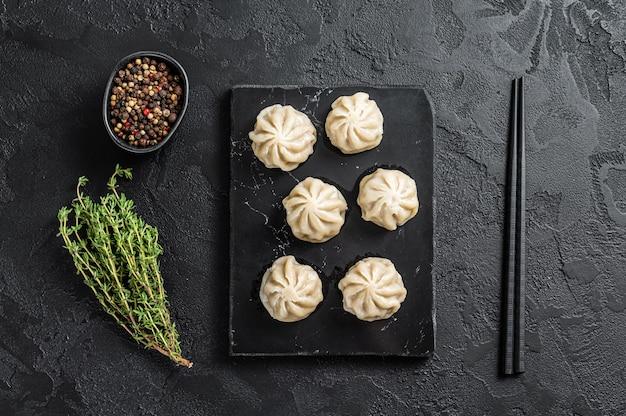 Boulettes de baozi chinois sur une planche de marbre. fond noir. vue de dessus.