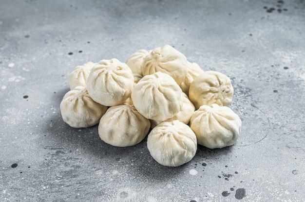 Boulettes de baozi non cuites surgelées farcies de viande. fond gris. vue de dessus.
