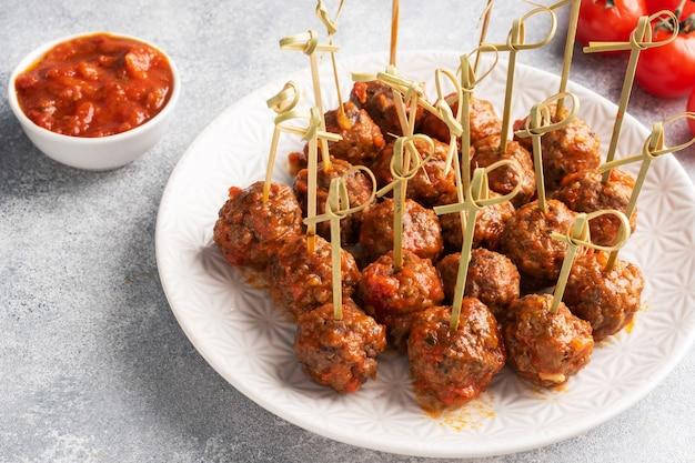 Boulettes de bœuf cuites à la sauce tomate sur une assiette sur des brochettes barbecue