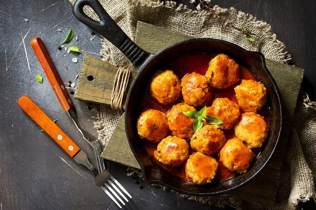 Boulettes de boeuf maison à la sauce tomate dans une poêle à frire sur une table en pierre sombre mise à plat