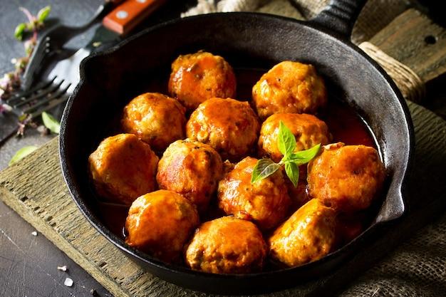Boulettes de boeuf maison à la sauce tomate dans une poêle sur une table en pierre sombre