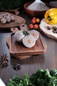 Boulettes de carottes crues sur la table en bois avec mini boulettes de paprika et mini tomate