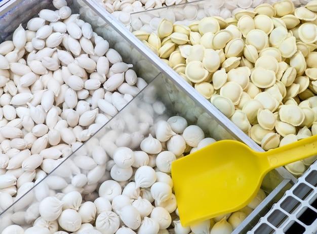 Boulettes congelées vendues au poids dans un récipient de réfrigérateur sur un comptoir de magasin