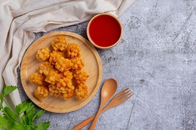 Boulettes de crevettes couvertes de panées frites sur la surface sombre.