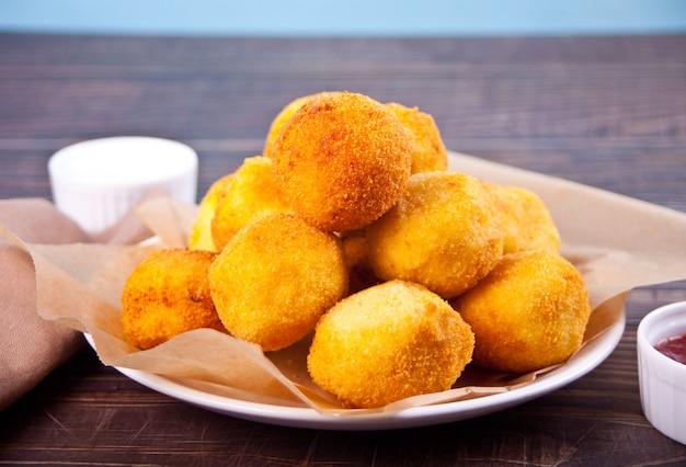 Boulettes de croquettes de pommes de terre dans l'assiette et trempette des sauces.