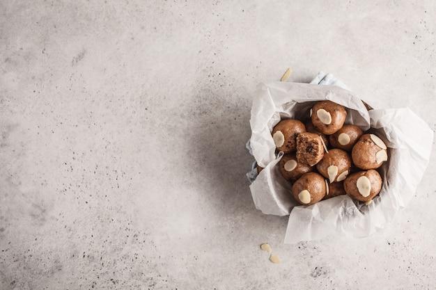 Boulettes crues de noix et de cacao sains végétaliens, vue de dessus, espace copie.