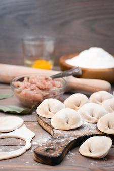 Boulettes crues sur la planche à découper et ingrédients pour leur préparation: farine, oeuf, viande hachée sur une table en bois
