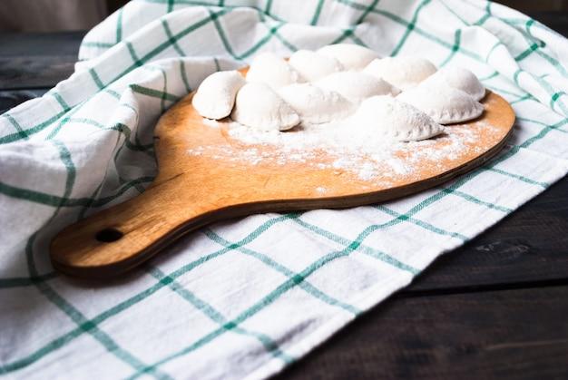 Boulettes crues saupoudrées de farine sur une planche de cuisine et une serviette à rayures