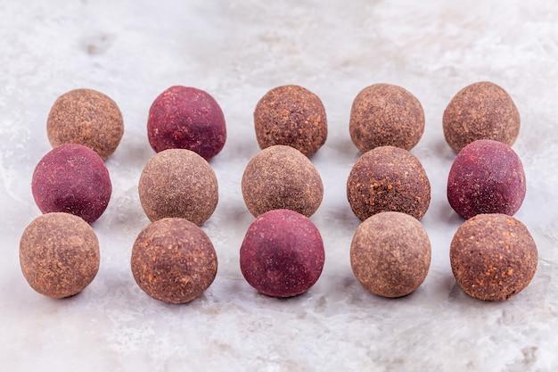 Boulettes d'énergie de cacao végétalien cru fait maison se trouvent sur une rangée