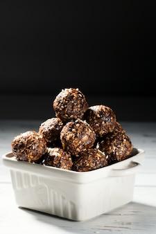 Boulettes d'énergie végétaliennes faites maison avec des flocons d'avoine, des noix, des dattes et du sésame
