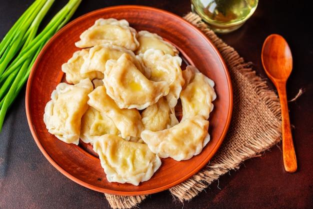 Les boulettes faites bouillies avec une farce avec de l'huile et des oignons verts sur une table sombre. il peut être utilisé comme arrière-plan