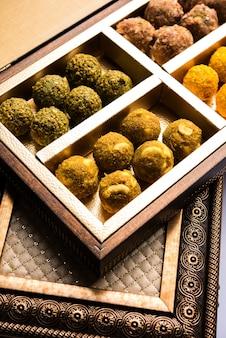 Boulettes de flocons d'avoine aux dattes ou fruits secs laddu dans une assiette d'emballage de boîte-cadeau, mise au point sélective