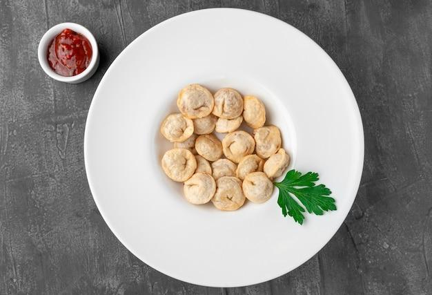 Boulettes frites. dans une grande assiette blanche. a côté d'une assiette se trouve une saucière. décoré avec du persil. vue d'en-haut. fond de béton gris.