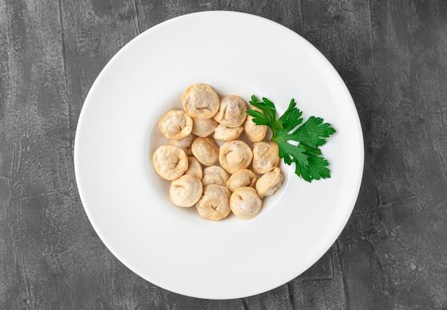 Boulettes frites. dans une grande assiette blanche. décoré avec du persil. vue d'en-haut. fond de béton gris.