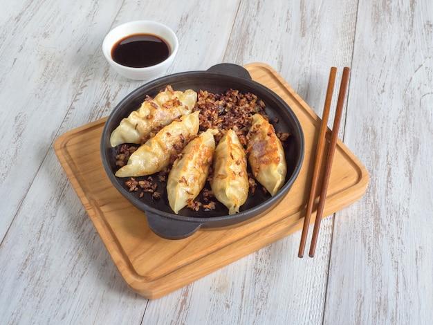 Boulettes frites gyoza dans une poêle, sauce soja et baguettes, vue de dessus.