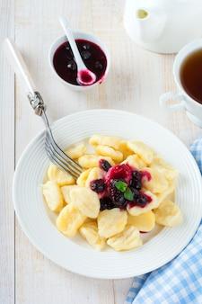 Boulettes de fromage, gnocchis à la sauce de cassis dans une assiette en céramique blanche pour un petit-déjeuner sain. mise au point sélective.