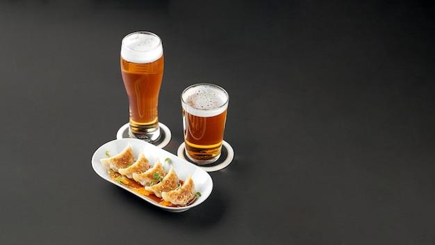 Boulettes de gedza avec de la bière sur fond gris