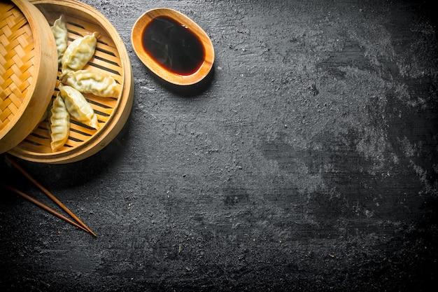 Boulettes de gedza traditionnelles chinoises chaudes en bambou vapeur avec sauce soja sur table rustique.
