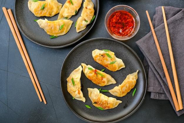 Boulettes de jiaozi gyoza cuites à la vapeur sur des assiettes noires avec sauce soja et huile de piment