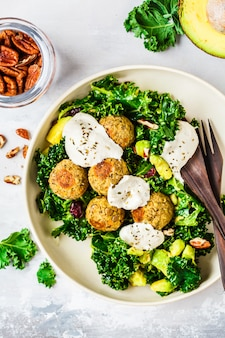 Boulettes de lentilles végétaliennes avec salade de chou vert, avocat et vinaigrette tahini dans un plat blanc, vue de dessus.