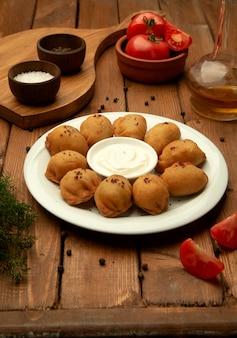 Boulettes de pelmeni frites servies avec du yaourt