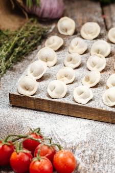 Boulettes de pelmeni semi-finies sur planche de bois