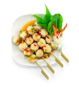 Boulettes de poisson grillées en brochettes avec sauce épicée décorer des légumes topview