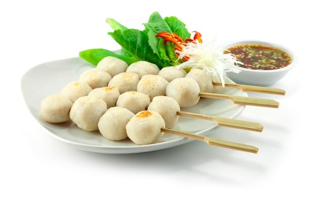 Boulettes de poisson grillées en brochettes servies avec une trempette épicée décorer des légumes sideview