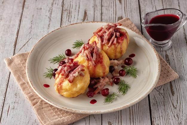 Boulettes de pommes de terre suédoises fraîchement préparées avec sauce aux canneberges sur fond clair.
