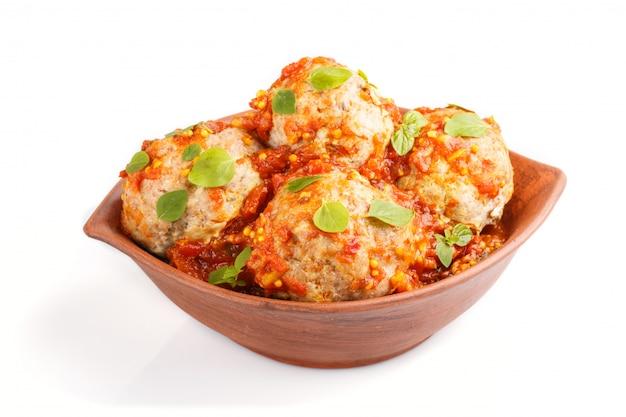 Boulettes de porc à la sauce tomate origan laisse des épices et des herbes dans un bol en argile isolé sur fond blanc