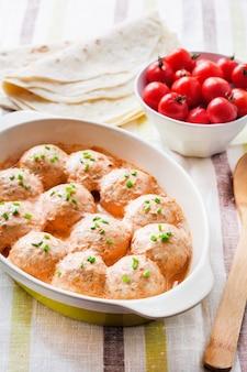 Boulettes de poulet maison cuites au four dans une sauce tomate crémeuse dans un plat de cuisson en céramique