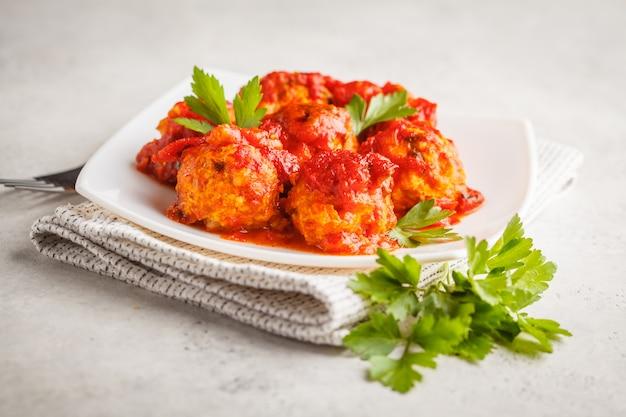 Boulettes de poulet à la sauce tomate dans une assiette blanche.