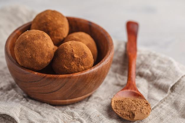 Boulettes de truffe raw energy végétaliennes saines avec caroube dans un bol en bois. concept de nourriture végétalienne saine.