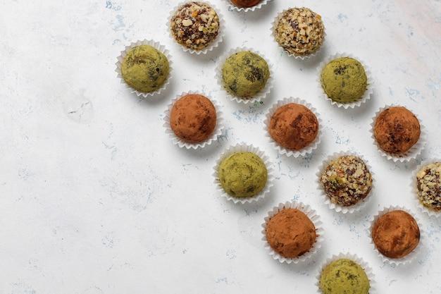 Boulettes de truffes énergétiques crues végétaliennes saines faites maison avec dattes et noix, poudre de matcha, poudre de cacao
