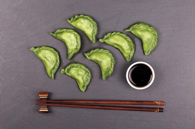 Boulettes vertes avec viande de bœuf ou purée de pommes de terre ou fromage cottage dans la pâte, accompagnées de spiruline